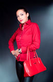 Bello brunette con la posizione rossa della camicia e del sacchetto Immagine Stock