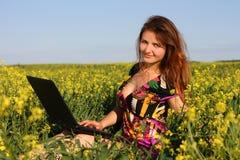 Bello brunette in un prato giallo con il computer portatile Fotografia Stock Libera da Diritti