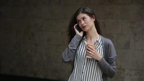 Bello buisnesswoman facendo uso dello smartphone con caffè, all'aperto stock footage