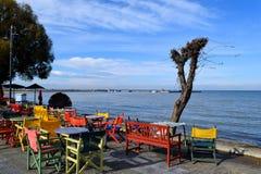 Bello caffè sulla spiaggia di Peraia Sedie variopinte e tavole davanti al mare ed al cielo blu fotografie stock