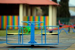 Bello campo da giuoco nell'asilo con pavimentazione molle, oscillazioni luminose, la rotonda ed il banco il giorno soleggiato Pos fotografie stock libere da diritti