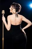 Bello cantante sorridente della giovane donna che tiene micr dorato dell'annata fotografie stock libere da diritti