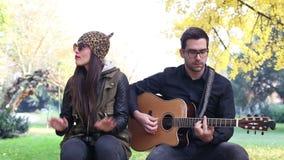 Bello canto della donna mentre uomo bello che gioca chitarra video d archivio