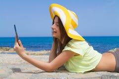 Bello castana adolescente facendo uso di una compressa dal Fotografie Stock Libere da Diritti