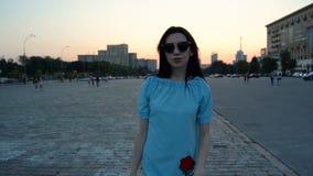 Bello castana alla moda in vetri scuri ed in un vestito blu va sulla macchina fotografica nella sera la città archivi video