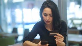 Bello castana caucasico in vestito nero alla moda che prova a fare un pagamento dal suo smartphone sui precedenti dell'ufficio archivi video