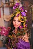 Bello castana con i fiori porpora in suoi capelli Immagini Stock Libere da Diritti
