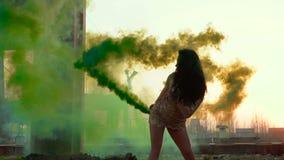 Bello castana nel dancing del vestito con il fumo verde al rallentatore video d archivio