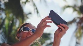 Bello castana in occhiali da sole che prendono selfie con il telefono cellulare sotto le palme Feste di vacanza 1920x1080 stock footage
