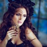 Bello castana sensuale con una corona del nero fiorisce il sittin Fotografia Stock