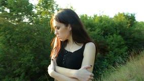 Bello castana solo in vestito nero sta sulla via fra gli alberi ed il Sun stock footage
