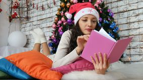 Bello castana in un cappello di Santa sta trovandosi sotto un albero di Natale brillantemente decorato e sta leggendo un libro Cr stock footage