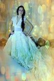 Bello castana in un vestito bianco nell'interno d'annata Immagini Stock