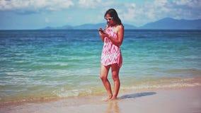 Bello castana in vestito rosso ed occhiali da sole che camminano sulla spiaggia sabbiosa e sul telefono cellulare di usi 1920x108 archivi video