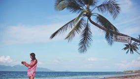 Bello castana in vestito rosso ed occhiali da sole che prendono foto con il telefono cellulare sulla spiaggia sabbiosa sotto le p video d archivio