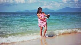 Bello castana in vestito rosso ed occhiali da sole che prendono selfie sulla spiaggia sabbiosa 1920x1080 stock footage
