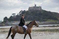 Bello cavallo da equitazione del cavaliere del cavallo maschio sulla spiaggia in abbigliamento tradizionale di guida con il suppo Fotografie Stock