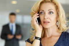 Bello cellulare sorridente biondo di conversazione della donna di affari fotografia stock libera da diritti