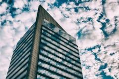 Bello cielo nuvoloso riflesso su costruzione corporativa immagine stock libera da diritti