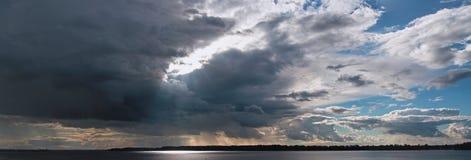 Bello cielo sopra il fiume con luce solare che attraversa le nuvole di tempesta fotografia stock libera da diritti
