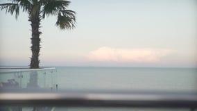 Bello colpo costante del tramonto caldo di crepuscolo di sera a vista sul mare dal balcone della finestra di vetro del tetto con  stock footage