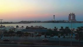 Bello colpo del corniche della città di Abu Dhabi e della spiaggia al tramonto - Marina Mall stock footage