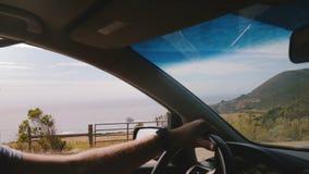 Bello colpo dell'in-automobile del volante della tenuta dell'uomo che guida seguendo la linea soleggiata incredibile strada della stock footage