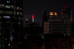 Bello colpo delle torri di Abu Dhabi alla notte con la bandiera dei UAE visualizzata su uno schermo immagini stock