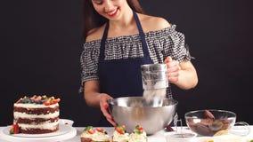 Bello confettiere femminile che aggiunge gli ingredienti per la preparazione di pasta, dolce bollente archivi video