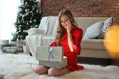 Bello contenitore di regalo di apertura della giovane donna a casa fotografia stock