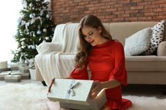 Bello contenitore di regalo di apertura della giovane donna a casa fotografia stock libera da diritti