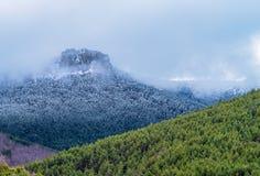 Bello contrasto delle montagne coperte da nebbia e da neve un giorno di molla immagine stock libera da diritti