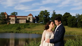 Bello coppie, sposo e sposa romantici di nozze abbraccianti vicino al vecchio castello sul tramonto stock footage