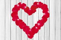 Bello cuore dei petali di rosa rossa sulle sedere di legno del primo piano di struttura Fotografie Stock