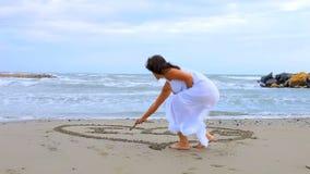 Bello cuore della pittura della donna sulla sabbia che dice ti amo archivi video