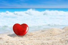 Bello cuore rosso di giorno di biglietti di S. Valentino su una spiaggia di sabbia bianca tropicale fotografie stock libere da diritti