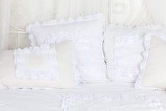 Bello e delicatamente il bianco ha merlettato i cuscini sul letto. Immagini Stock