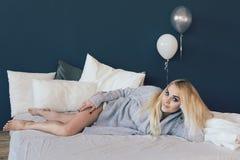Bello e giovane donna in maglione grigio sul letto Fotografie Stock Libere da Diritti