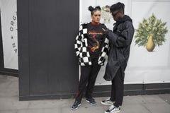 Bello e inblack e camice alla moda della donna che posano durante la settimana di modo di Londra Eudon Choi esterno Fotografia Stock Libera da Diritti