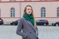 Bello e ragazza in un cappotto cammina sulla città quotidiana Immagine Stock