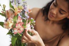 Bello fiorista femminile africano che fa mazzo dei fiori Fuoco sui alstroemerias Fotografie Stock