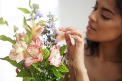 Bello fiorista femminile africano che fa mazzo dei fiori Fuoco sui alstroemerias Fotografia Stock
