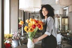Bello fiorista in grembiule che crea grande mazzo dei tulipani variopinti in vaso Giovane ragazza afroamericana che sta con fotografia stock