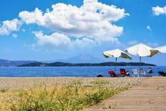 Bello fondo della spiaggia con le sedie e l'ombrello, Grecia Khalkidhiki immagini stock