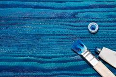 Bello fondo di legno dipinto con pittura blu luminosa apra un tubo di pittura e delle spazzole Fotografia Stock Libera da Diritti