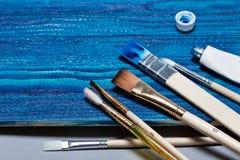 Bello fondo di legno dipinto con pittura blu luminosa apra un tubo di pittura e delle spazzole Immagine Stock Libera da Diritti