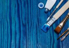 Bello fondo di legno dipinto con pittura blu luminosa apra un tubo di pittura e delle spazzole Fotografia Stock