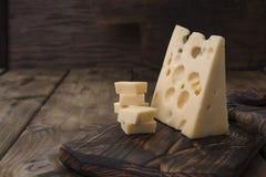 Bello formaggio olandese con i fori, un prodotto lattiero-caseario sano Alimento saporito Foto stile country Posto per testo Copi Immagine Stock Libera da Diritti