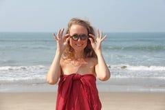 Bello freak della ragazza in un vestito e nei capelli biondi rossi, sui precedenti del mare Ragazza di estate in vetri di legno r immagini stock libere da diritti