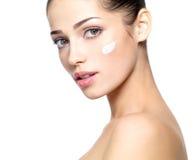 Bello fronte della donna con crema sulla guancica. fotografie stock